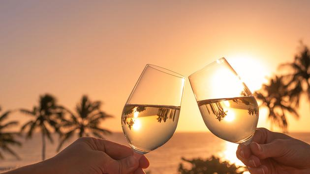 Cheers with wine glasses in a beautiful sunset setting (Photo via kieferpix / iStock / Getty Images Plus)