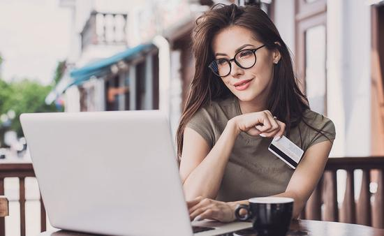 Woman is online with laptop computer and credit card (Photo via Poike / iStock / Getty Images Plus)