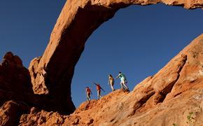 A family hiking Arches National Park near Moab, Utah