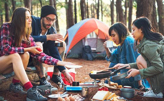 Friends camping in the forest (Photo via Rawpixel / iStock / Getty Images Plus)