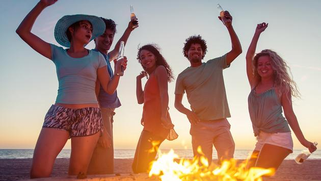 Group of friends with fire and music (Photo via oneinchpunch / iStock / Getty Images Plus)