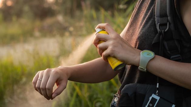 Woman using anti mosquito spray outdoors at hiking trip. (Photo via  Photoboyko / iStock / Getty Images Plus)