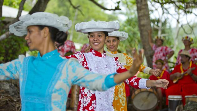 Local women in colorful dresses dance on the island of Rurutu