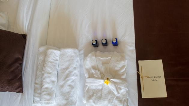 Top view of rolled towels and bathrobe on bed in hotel room.   (Photo courtesy of LightFieldStudios/ iStock / Getty Images Plus)