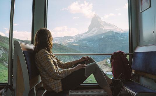 Young woman traveling on the train near Matterhorn, Swiss Alps