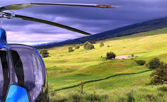 Blue helicopter on green slope under grey cloud.