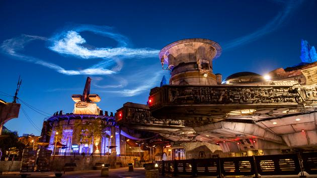 A vapor trail from SpaceX's Falcon 9 rocket hangs in the air as seen from Star Wars: Galaxy's Edge at Disney's Hollywood Studios at Walt Disney World Resort