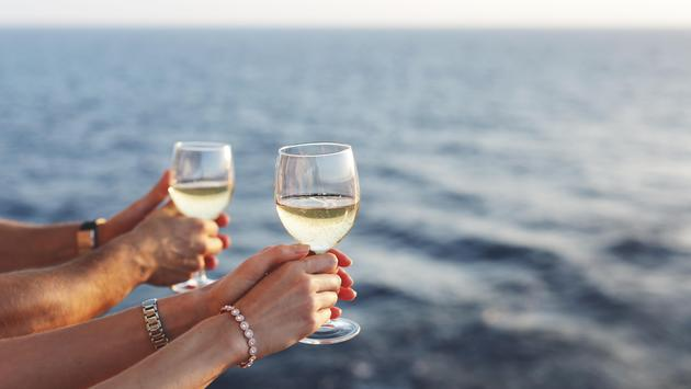 arms man and woman holding glasses with white wine