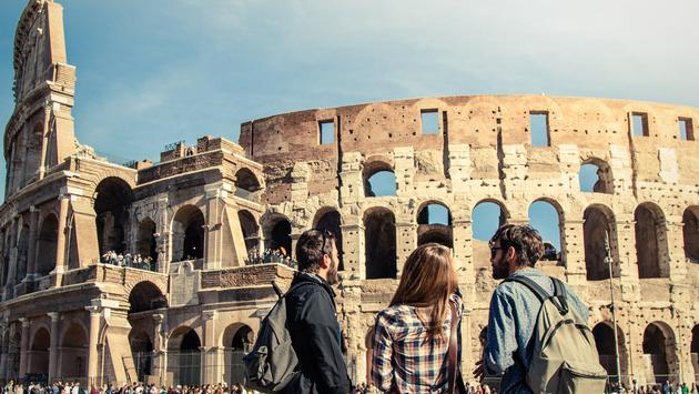 Three young friends tourists standing in front of Colosseum in Rome.(photo courtesy of TFILM / iStock / Getty Images Plus)
