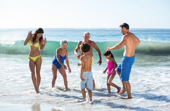 Multi-generational family group playing in the surf.
