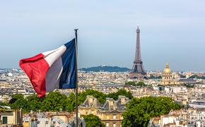 The French Flag waving with Paris and the Eiffel Tower in the background.
