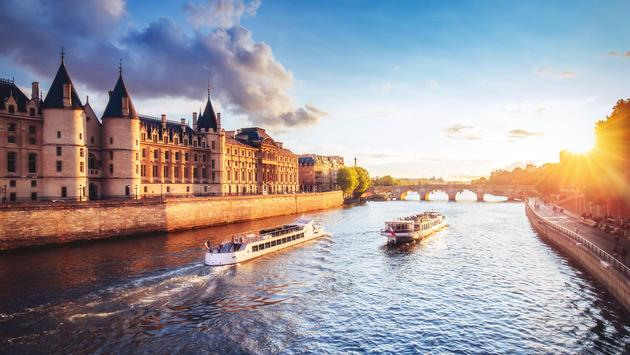 Dramatic sunset over river Seine in Paris, France, with Conciergerie and cruise boats.