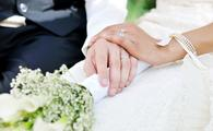 A husband and wife holding hands on their wedding day.