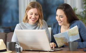 Friends using laptop to search travel