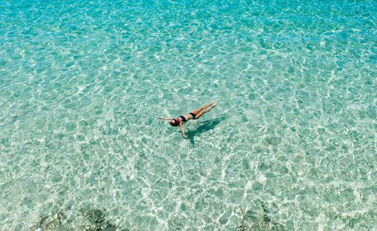Woman floating in Crystal Bay, Bali