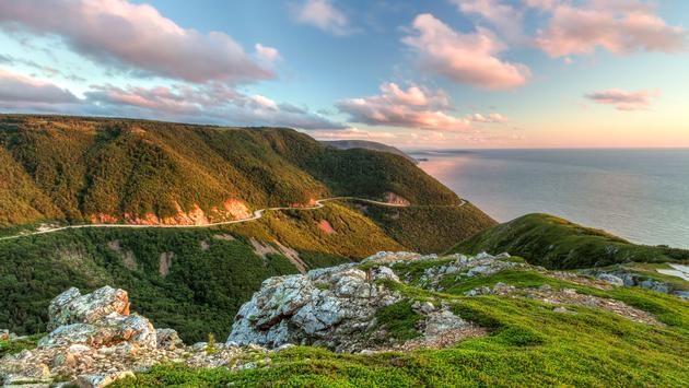 The winding Cabot Trail road seen from high above on the Skyline Trail at sunset in Cape Breton Highlands National Park, Nova Scotia (lightphoto / iStock / Getty Images Plus)