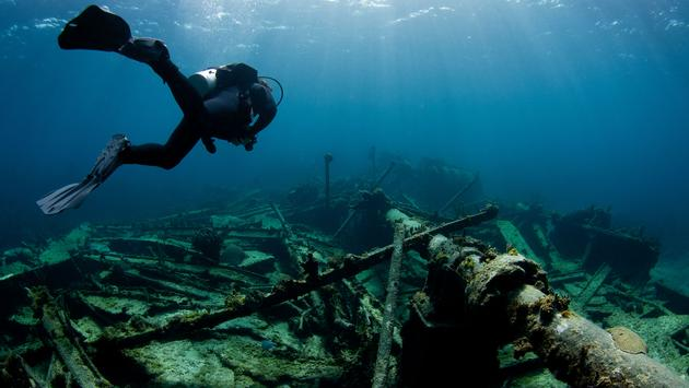 A scuba diver swims over a sunked shipwreck. (photo via ShaneGross / iStock / Getty Images Plus)