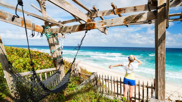 Young woman enjoying view of tropical beach on Eleuthera Bahamas (photo via shalamov / iStock / Getty Images Plus)