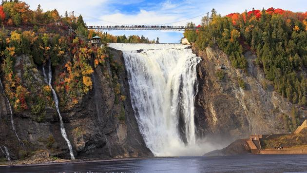 Montmorency Falls and Bridge in autumn with colorful trees, Quebec, Canada (Photo via Vladone / iStock / Getty Images Plus)