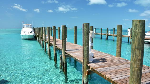 Yacht at the wooden jetty. Exuma, BahamasWooden pier. Exuma, Bahamas (photo via astra490 / iStock / Getty Images Plus)