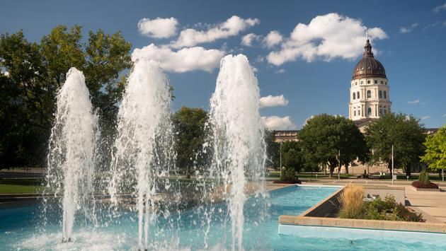 Soft clouds and blue skies appear over fountains and the capitol of Topeka, Kansas USA (photo via chrisboswell/ iStock / Getty Images Plus)