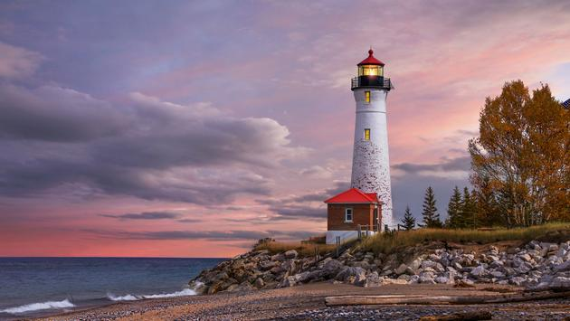 As daylight begins yielding to twilight, The Crisp Point Lighthouse at sunset on Lake Superior, Upper Peninsula, Michigan, USA - A one hour drive from Tahquamenon Falls, mostly dirt roads (photo via DougLemke / iStock / Getty Images Plus)