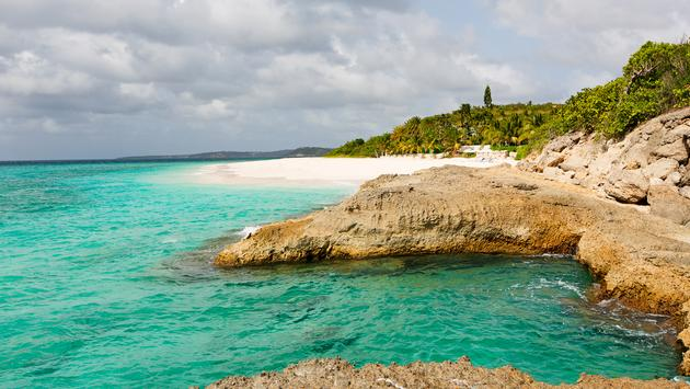 view at rugged rocky seashore and white sand empty beach at anguilla, island in caribbean sea (Photo via noblige / iStock / Getty Images Plus)