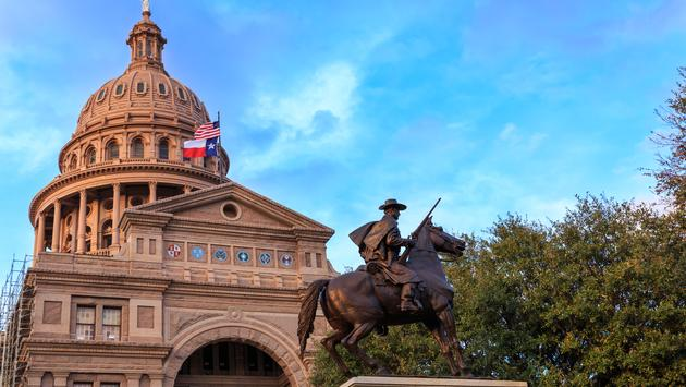 The Texas Ranger statue in front of the Texas Capital building in Austin, TX (photo via TriciaDaniel / iStock / Getty Images Plus)