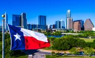 Texas flag flying in front of Austin Texas downtown skyline cityscape sunny perfect day (photo via RoschetzkyIstockPhoto / iStock / Getty Images Plus)