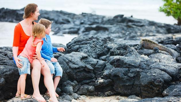 Mother and kids looking at endemic marine iguana at Galapagos islands (photo via shalamov/iStock/Getty Images Plus)