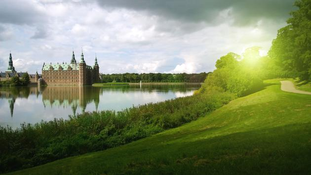 Frederiksborg castle in Denmark - the castle on the left, to the right a bright green lawn (photo via Kroshanosha / iStock / Getty Images Plus)