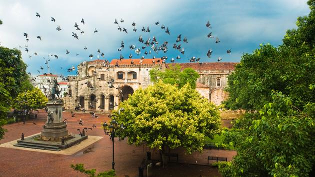 Doves flying over main square with Columbus statue, Santo Domingo, Dominican Republic (photo via 3dan3 / iStock / Getty Images Plus)