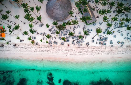 Aerial view of tropical island beach. Dominican Republic. (photo via valio84sl / iStock / Getty Images Plus)