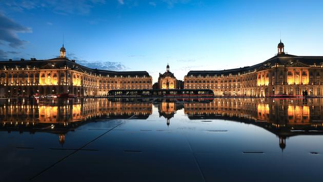 Reflection of Place De La Bourse and tram in Bordeaux, France. A Unesco World Heritage (photo via EoNaYa / iStock / Getty Images Plus)