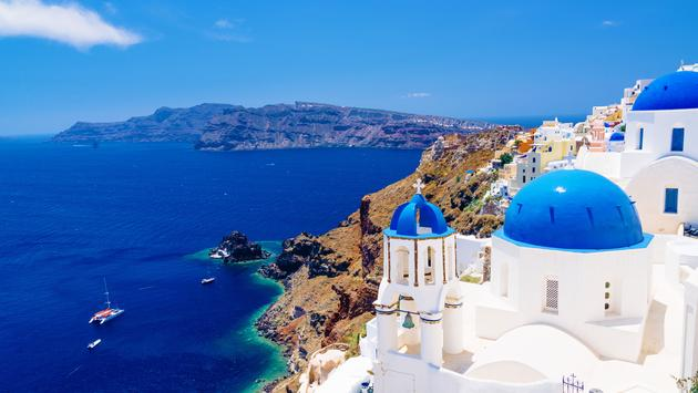 White architecture and churches with blue domes, Oia, Santorini, Greece (photo via Aetherial/iStock/Getty Images Plus)