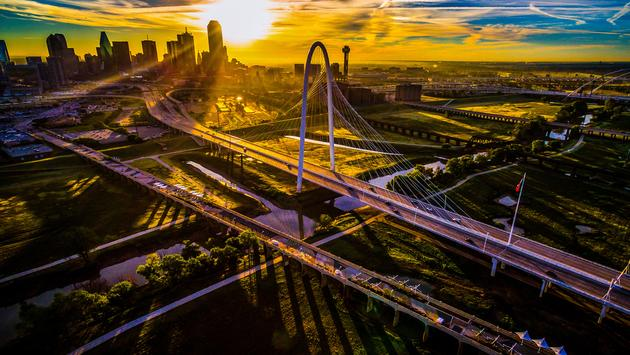 Sun rays glow across Dallas , Texas , USA Aerial Drone View high above North Texas Cityscape at sunrise lots of Bridge and Towers skyline skyscrapers with orange golden hour sun rays (photo via RoschetzkyIstockPhoto / iStock / Getty Images Plus)
