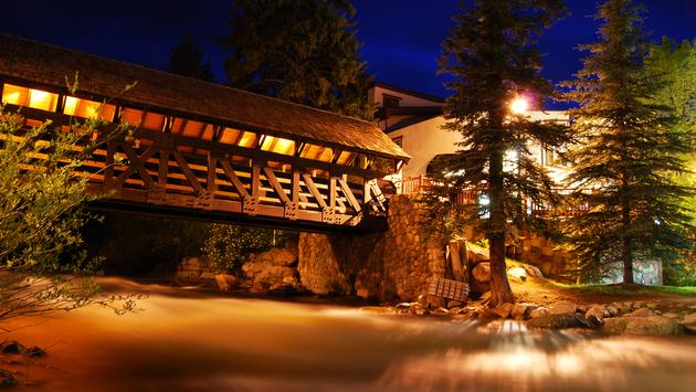 This covered bridge is lit up at night in Vail, Colorado, a popular summer and winter vacation destination for mountain bikers, skiers, and snowboarders. (photo via brianbalster / iStock / Getty Images Plus)