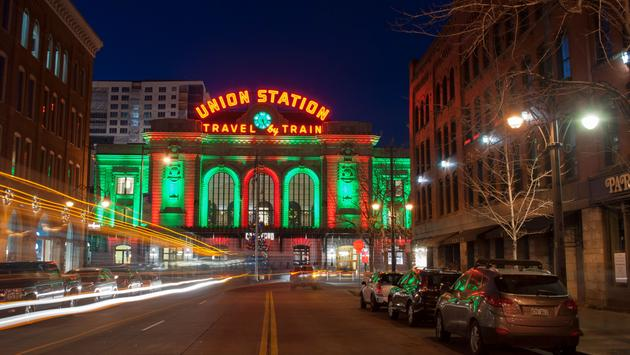 View of Union Station in downtown Denver, Colorado, taken at night from the middle of a street. The train station is lit up for the Christmas Holiday season (photo via JuliScalzi / iStock / Getty Images Plus)