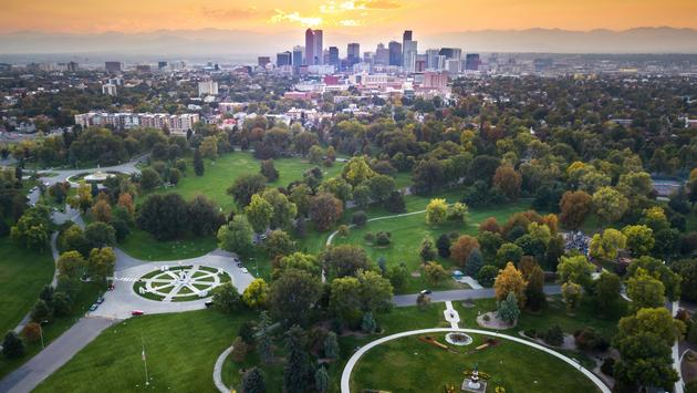 Sunset over Denver cityscape, aerial view from the city park (photo via Creative-Family / iStock / Getty Images Plus)