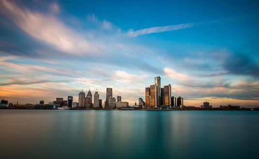A panorama of the Detroit, Michigan skyline, as seen from across the Detroit River in Windsor, Ontario. (photo via Steven_Kriemadis / iStock / Getty Images Plus)