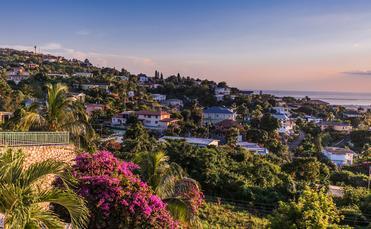 Kingston city in Jamaica sunset (photo via GummyBone / iStock / Getty Images Plus)