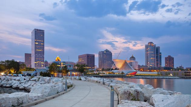 Image of Milwaukee skyline at twilight with city reflection in lake Michigan and harbor pier. (photo via RudyBalasko / iStock / Getty Images Plus)