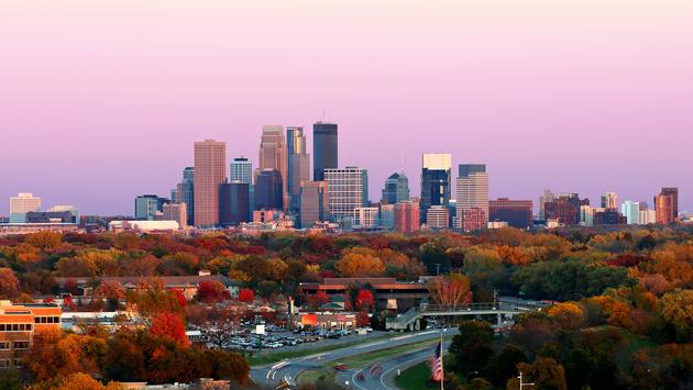 A view of the Minneapolis skyline during the peak of color in the Fall from Plymouth, Minnesota. This image was captured right at sunset. The city of Golden Valley and highway 55 appear in the foreground. (photo via rasilja / iStock / Getty Images Plus)