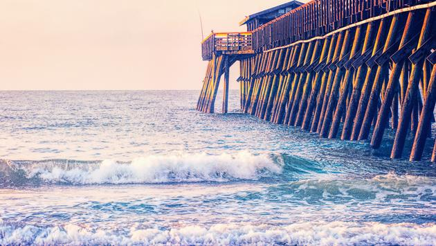 One man is fishing as the sun comes up over the Atlantic Ocean at the Myrtle Beach State Park Pier in South Carolina, USA.This is computer generated art from a photograph. (LCBallard / iStock / Getty Images Plus)