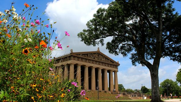The Parthenon Pavilion housing the Athena statue in Centennial Park in Nashville Davidson County Tennessee during a summer day showing the blue sky green grass and flowers in the foreground during the day showing the architecture of the building at this t