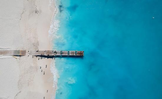Drone photo of pier in Grace Bay, Providenciales, Turks and Caicos. The caribbean blue sea and white sandy beaches can be seen (photo via JoaoBarcelos / iStock / Getty Images Plus)
