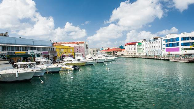 Main water canal with ships and shops in Bridgetown, capital of Barbados. Caribbean (photo via Fyletto / iStock / Getty Images Plus)