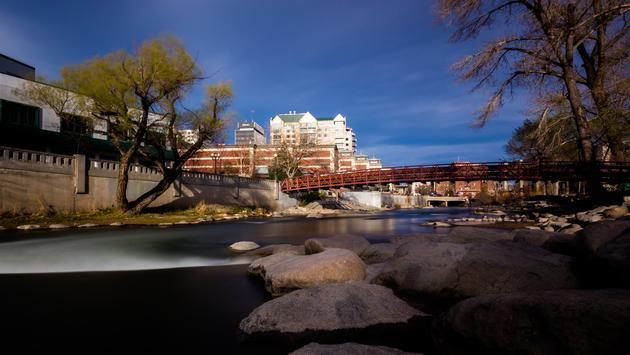 Downtown Reno, Nevada Riverwalk with Truckee River and large granite stone son the shoreline. (photo via ddub3429 / iStock / Getty Images Plus)