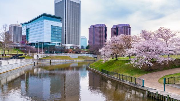 Richmond,Virginia morning city skyline along the James River near Brown's Island and Tredegar St during cherry blossoms. (photo via pabradyphoto / iStock / Getty Images Plus)