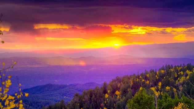 New Mexico fall mountain sunset featuring golden aspens and rays of sunlight (photo via Dean_Fikar / iStock / Getty Images Plus)